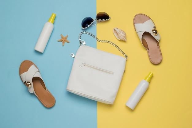 Damestas, schoenen, crèmes en accessoires op een gele en blauwe achtergrond. vakantieconcept. plat leggen.