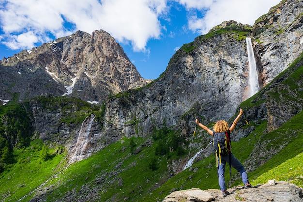 Damewandelaar die waterval op berg bekijken