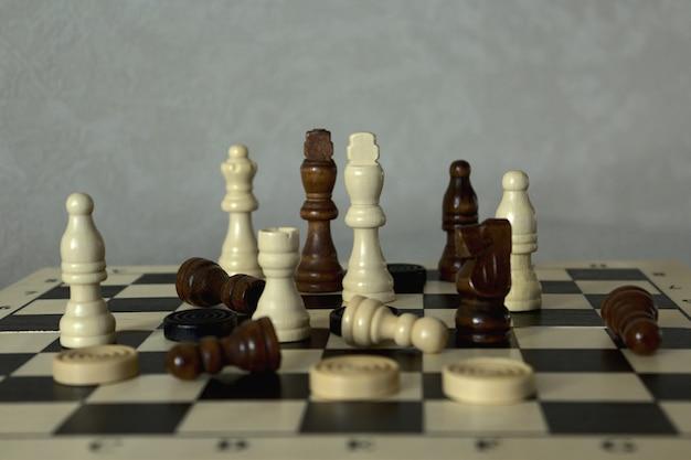 Dammen en schaakstukken op het schaakbord