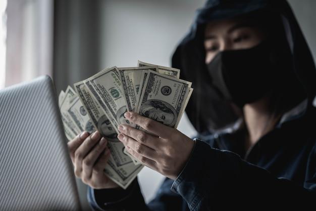Dangerous hooded hacker hield het geld vast na het succesvol hacken.