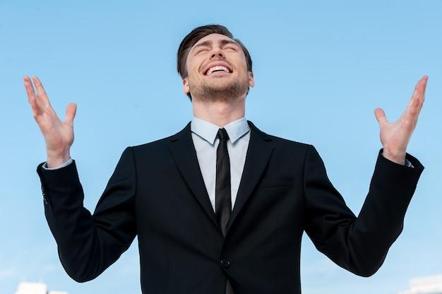 Dank aan allah! knappe jonge man in pak die handen opsteekt en glimlacht terwijl hij tegen de blauwe hemel staat