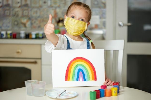 Dank aan nhs. kid in beschermend masker schilderen van de regenboog tijdens covid-19 quarantaine thuis. coronavirus covid-19 uitbraak.