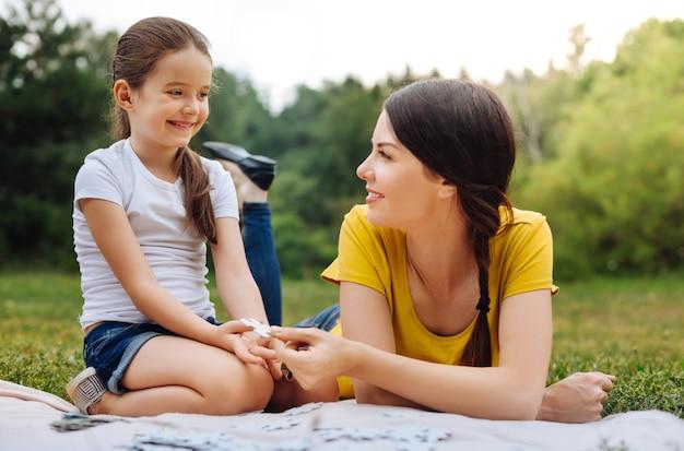 Dank je. vrolijk meisje dat een ontbrekend stukje van een puzzel uit haar moeders handen neemt terwijl ze een puzzel doen op een picknick in het park