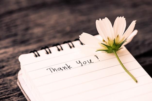 Dank u tekst op een wit pagina notitie boek met romantische witte bloem