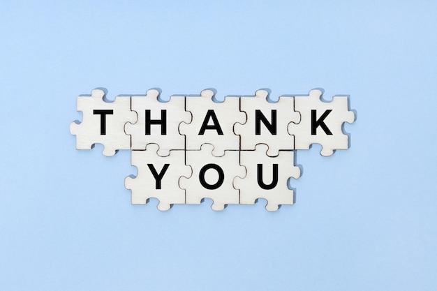Dank u zin op houten puzzelstukjes geïsoleerd op blauwe achtergrond. bovenaanzicht
