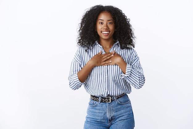 Dankbaar gelukkig glimlachend afrikaans amerikaans meisje dat prijs ontvangt dankbaar drukkende handpalmen borst grijnzend verbaasd kijkend waardering verrukking, staand blij verbaasd geamuseerd witte muur