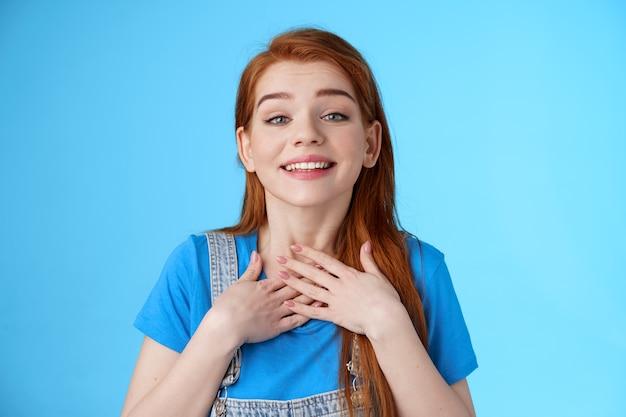 Dankbaar oprecht schattig charmant roodharige vrouw die vrienden bedankt, glimlachend opgetogen waardeert mooi teder gebaar, druk op handpalmen borsthart, dankbaar, kijk bewondering en liefde, sta blauwe achtergrond