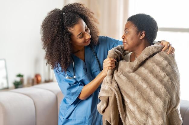Dankbaar voelen. oudere zieke dame die dankbaar is voor de zorgzame, aangename verpleegster in het verpleeghuis