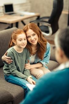 Dankbaar voor hulp. opgetogen aardige moeder en dochter die naar hun dokter kijken terwijl ze dankbaar zijn voor hulp