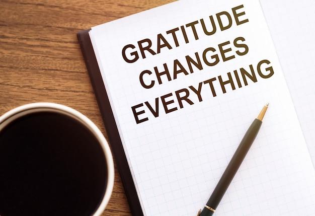 Dankbaarheid verandert alles - motivatie schrijven op een notitieboekje op tafel
