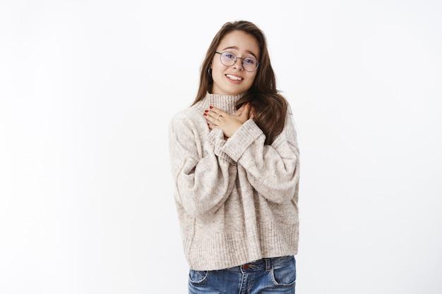 Dankbare charmante vrouw die tedere woorden waardeert die handen op de borst houden als dank van hart en ziel die wordt aangeraakt en dankbaar zich gelukkig voelt door hartverwarmende gebaren over grijze muur.