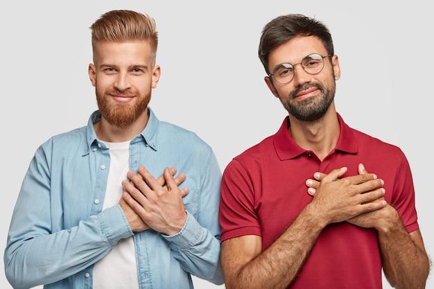 Dankbare gebaarde broers poseren tegen de witte muur