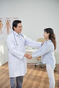 Dankbare gelukkige vrouw die de hand schudt van haar arts die haar waardering toont
