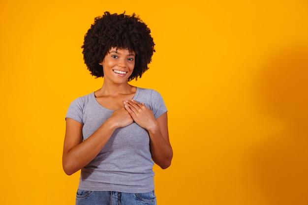 Dankbare hoopvolle gelukkige zwarte vrouw hand in hand op de borst voelt zich blij dankbaar pleased