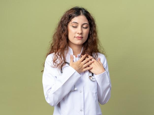 Dankbare jonge vrouwelijke arts met een medisch gewaad en een stethoscoop die de handen op de borst houdt en een godzijdank gebaar doet met gesloten ogen geïsoleerd op een olijfgroene muur met kopieerruimte