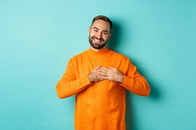 Dankbare man glimlachend, hand in hand op hart, dank u gebaar, geraakt gevoel met geschenk, staande op turkooizen achtergrond.