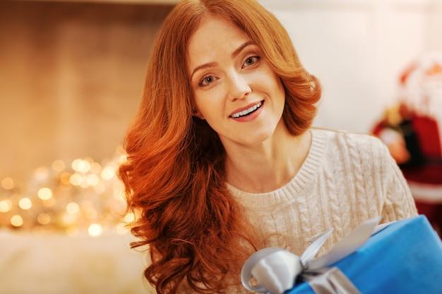 Dankbare ogen. verbaasde roodharige vrouw met ogen vol verbazing na het ontvangen van een groot kerstcadeau thuis.