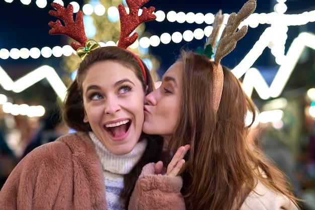 Dankbare vrouw die een kus op kerstmarkt geeft