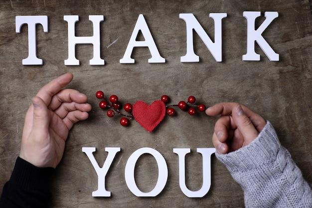 Dankwoord van witte houten letters op tafel en handen