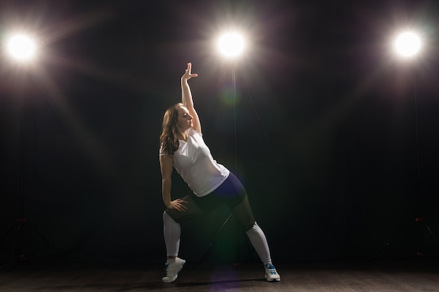 Dans, hiphop, jazzfunk en mensenconcept - flexibele jonge vrouw die in de duisternis onder het licht danst.