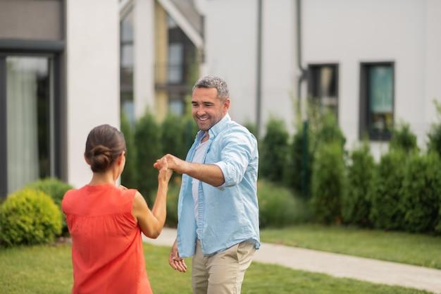 Dans tijd. grijsharige knappe man danst met zijn mooie donkerharige vrouw