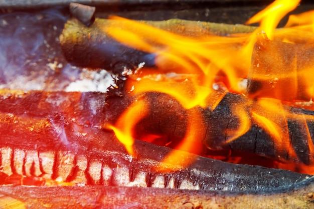 Dans van vlammen tegen een donkere achtergrond, houtgestookte grill in de open haard.