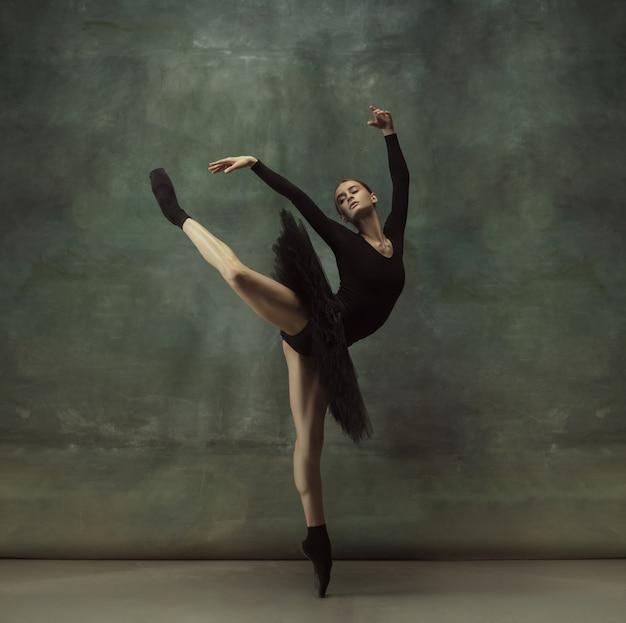 Dansavond. sierlijke klassieke ballerina dansen, poseren geïsoleerd op donkere studio achtergrond. elegantie zwarte tutu. genade, beweging, actie en bewegingsconcept. ziet er gewichtloos, flexibel uit. modieus.
