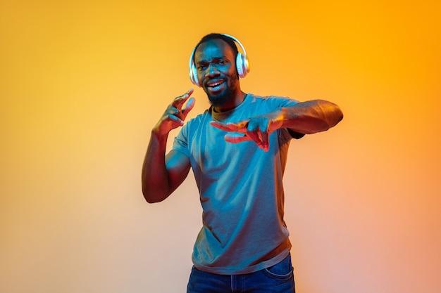 Dansen, blij. portret van een afro-amerikaanse man in een koptelefoon op een oranje achtergrond met kleurovergang in neonlicht. mooi afromodel. concept van menselijke emoties, gezichtsuitdrukking, verkoop, advertentie. kopieerruimte.