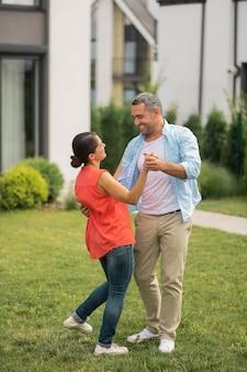 Dansen met vrouw. grijsharige vrolijke man danst met vrouw en glimlacht terwijl hij zich gelukkig voelt