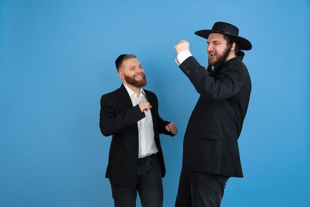 Dansen, plezier maken. portret van een jonge orthodoxe joodse mannen geïsoleerd op blauwe muur. purim, zaken, festival, vakantie, viering pesach of pesach, jodendom, religie concept.