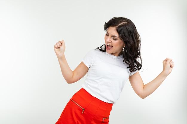 Dansend donkerbruin meisje in een wit t-shirt