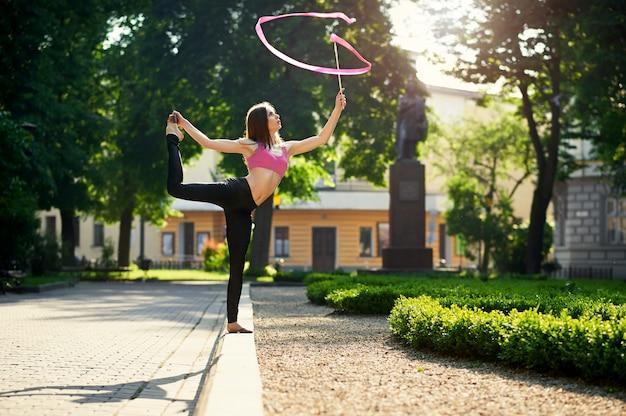 Dansend meisje met een lint in het stadspark.