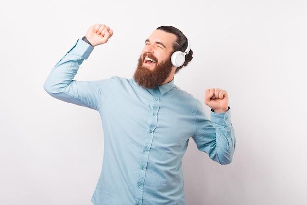 Dansende bebaarde man draagt een koptelefoon op een witte achtergrond.