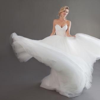 Dansende jonge bruid in luxe trouwjurk. mooi meisje in het wit. emoties van geluk, gelach en glimlach, grijze achtergrond