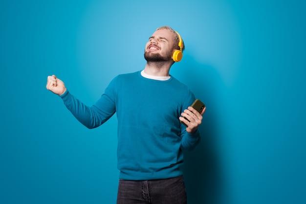 Dansende man met een telefoon luistert naar muziek met behulp van een koptelefoon en glimlach op een blauwe muur in de studio