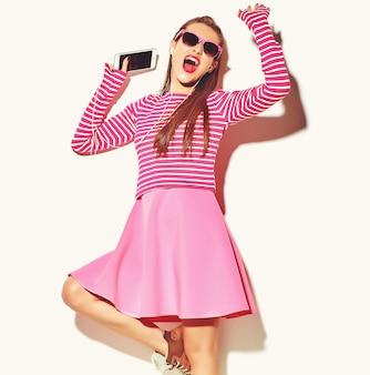 Dansende mooie gelukkige schattige lachende sexy brunette vrouw meisje in casual kleurrijke roze zomer kleding met rode lippen geïsoleerd op wit luisteren naar muziek