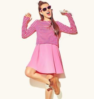 Dansende mooie gelukkige schattige lachende sexy brunette vrouw meisje in casual kleurrijke roze zomer kleding met rode lippen