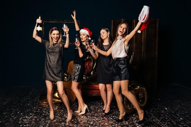Dansende mooie vrouwen met champagne het vieren kerstmis