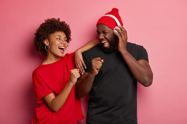 Dansende vrouw en man die vol energie zijn, lachen en dansen, luisteren naar muziek