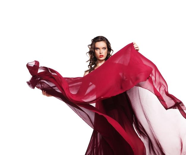 Dansende vrouw in rode jurk die op de wind vliegt