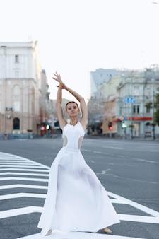 Danseres in een witte jurk in de stad