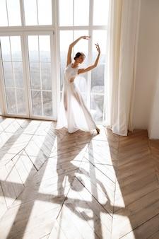 Danseres in witte jurk in de buurt van venster