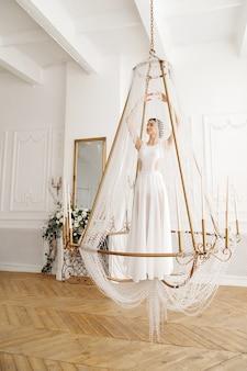 Danseres in witte jurk in een kroonluchter in een lichte studio