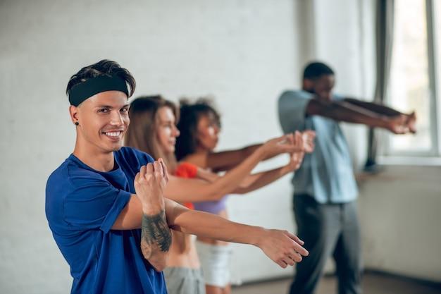 Dansers doen voor de repetitie versterkende fysieke oefeningen