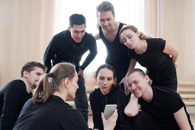 Dansers kijken naar iets op smartphone