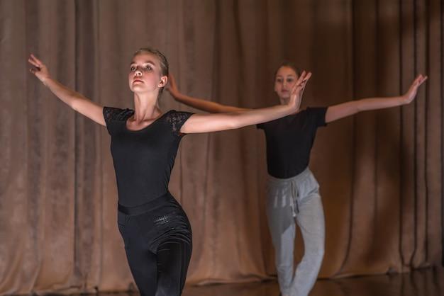 Dansers van jonge meisjes trainen dansbewegingen op het podium.