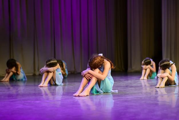 Dansersmeisjes zitten op het podium, dramatische dans