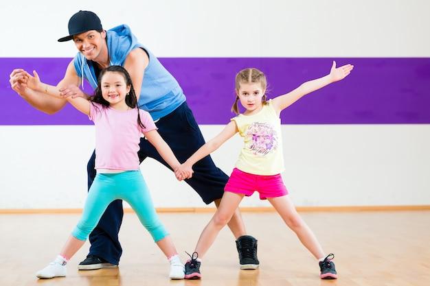 Dansleraar die kinderen zumba-danslessen geeft