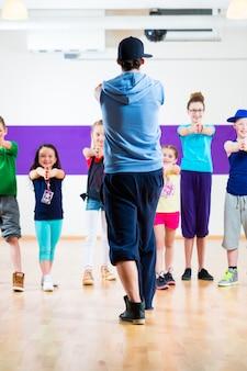 Dansleraar die kinderen zumba-fitnessles geeft