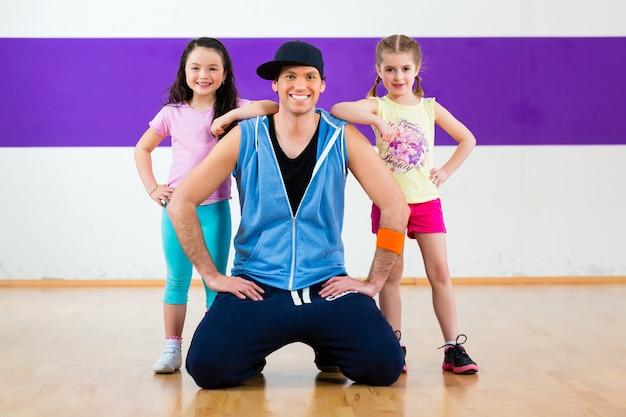 Dansleraar geeft kinderen zumba fitnessles i